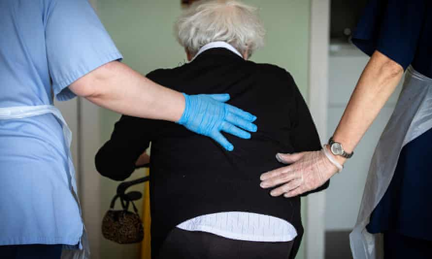 A resident is helped by care workers.