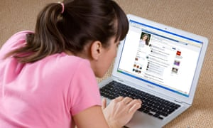 young woman looking at Facebook website on laptop computer.