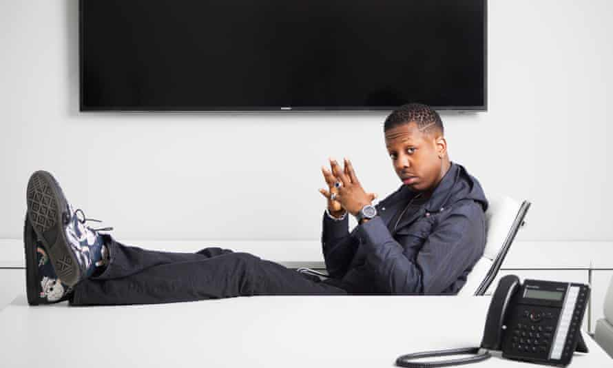 Jamal Edwards leaning back in an office chair with his feet (in trainers) on the desk and finger tips together