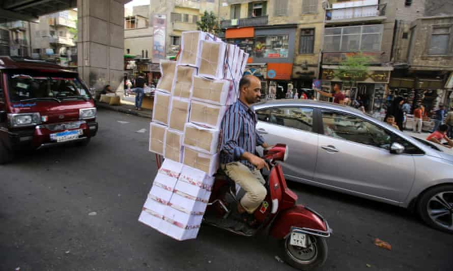 Chaotic … a man carries shoe boxes on a Vespa in downtown Cairo.
