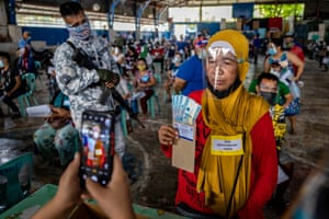 Manila, Philippines. A social worker takes a picture of a person receiving cash aid for those out of work during the coronavirus pandemic