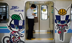 A commuter stands on a train decorated with Tokyo Olympic and Paralympic Games mascots in Tokyo, Japan.