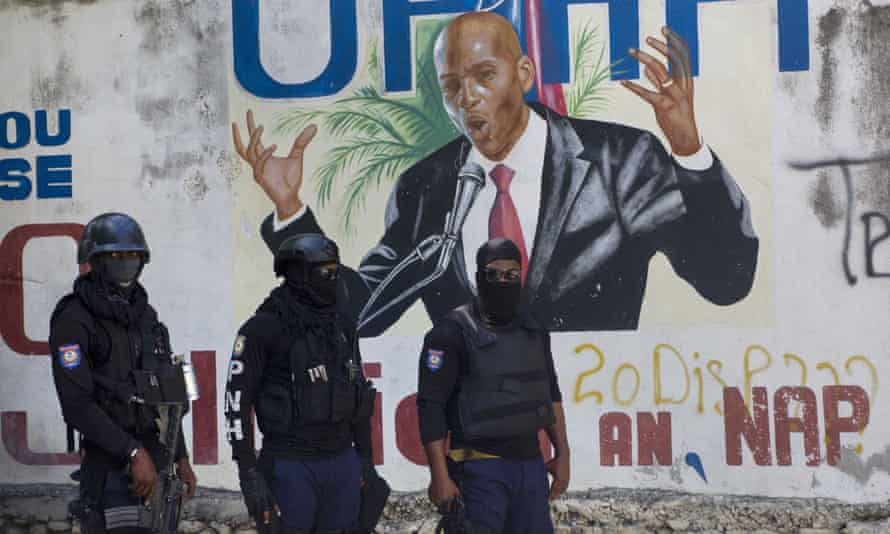 Police stands before a mural of Haiti's President Jovenel Moïse, who was assassinated last week, days after another 15 Haitians were gunned down.