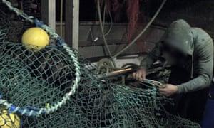 A worker mends nets on an Irish trawler