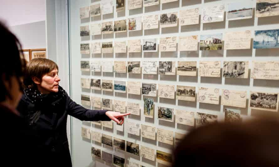 Visitors look at a wall of postcards in the new exhibition, German Colonialism. Fragments Of Its History And Present, at the German Historical Museum.