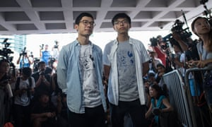 Student pro-democracy activists Nathan Law (L) and Joshua Wong (R) speak to the media outside Hong Kong's high court on the day of their sentencing