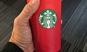 This November 9, 2015 photo shows a consumer holding the 2015 Starbucks holiday cup in Washington, DC. The unadorned red cup which debuted November 1 came under fire for its lack of design. Creating a culture of belonging, inclusion and diversity is one of the core values of Starbucks, and each year during the holidays the company aims to bring customers an experience that inspires the spirit of the season, the company wrote in a press release. Starbucks will continue to embrace and welcome customers from all backgrounds and religions in our stores around the world.AFP PHOTO/ KAREN BLEIERKAREN BLEIER/AFP/Getty Images
