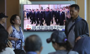 People watch a TV screen showing North Korean leader Kim Jong-un, centre, visiting the Kumsusan Palace of the Sun.