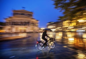 Frankfurt, Germany: A man with umbrella rides his bike in front of the Old Opera in the rain