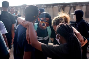 """Protesters embrace as they take to the highway to protest and mourn George Floyd, a black man who died after a white policeman kneeled on his neck for several minutes during the """"Justice 4 George Floyd"""" event in Houston, Texas on May 29, 2020. - Demonstrations are being held across the US after George Floyd died in police custody on May 25."""