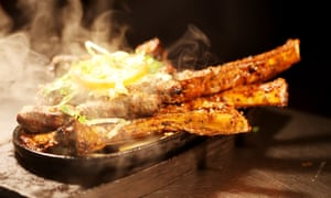 A dish, steam coming off it, of lamb chops and dry meat at Tayyab's curry restaurant, Fieldgate street, London.