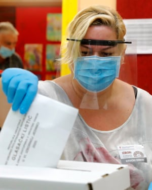 A voter wears a plastic face shield, a face mask and gloves as she casts her ballot for the Croatian parliamentary election