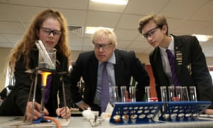 Boris Johnson watching students Ruby Culter and Matthew Upright performing a science experiment during his visit to Chulmleigh College in Devon.