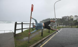 A man held by strong winds poses at Bondi beach on April 21, 2015 in Sydney, Australia. A second day of damaging winds and heavy rain have hit the New South Wales coast, dowing powerlines, cutting power to homes and causing delays for traffic and public transport.