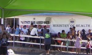 Children with their parents wait in line to get vaccinated outside a health clinic in Apia, Samoa after the government declared a state of emergency and mandated that everybody get vaccinated.