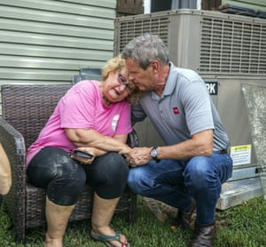 The Tennessee governor, Bill Lee, comforts Shirley Foster, who has just learned a friend died in the flooding.