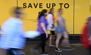Pedestrians walks past an advertisement outside a department store in Sydney, 5 October 2016.