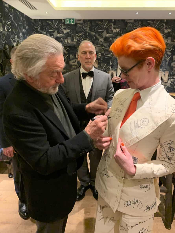 Robert De Niro signs Sandy Powell's suit.