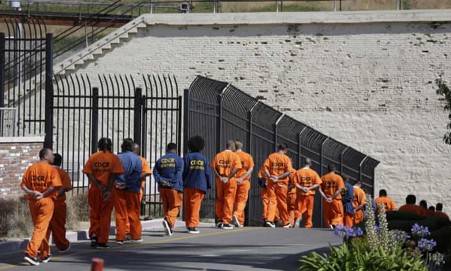 Incarcerated people walk in a line at San Quentin state prison in California.