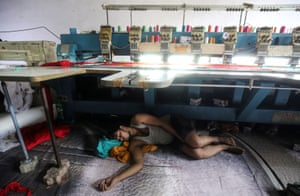 Mumbai, India A worker sleeps underneath an embroidery machine at a workshop