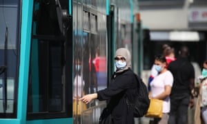 A passenger wearing a protective face mask boards a tram in Frankfurt