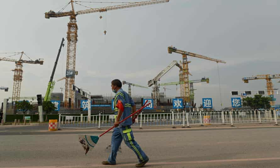 A man in work clothes carrying a rake walks in front of a series of cranes