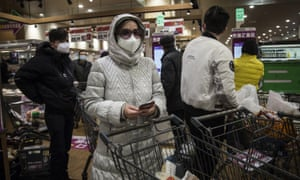 Residents wear protective mask as they line up to pay in the supermarket in Wuhan.