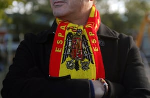 A supporter wears a scarf with a Franco-era flag outside the cemetery