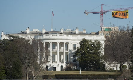 Greenpeace protesters unfold a bannerfrom atop a construction crane behind the White House Wednesday.