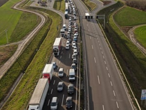 Vehicles wait in long lines to cross into Romania from Hungary at the Csanádpalota border crossing on 22 March, after Hungary closed its borders to all but its own citizens.