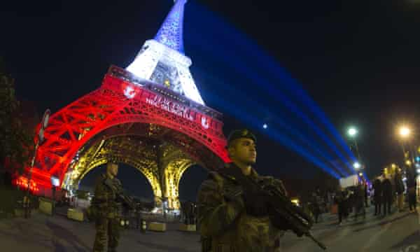 A French soldier enforces France's national security alert system in front of the Eiffel Tower.