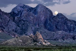 Moon over Baldy Peak and La Cueva west side of the Organ Mountains Desert Peaks National Monument near Las Cruces, New Mexico.