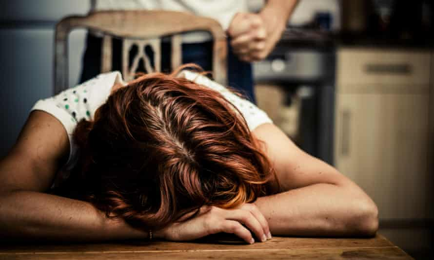 Woman crying in kitchen with abusive partner behind her