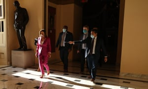 Speaker of the House Nancy Pelosi is accompanied by staff, security and press as she walks through the US Capitol before a series of votes on a $3tn economic package to aid for those affected by the novel coronavirus pandemic 15 May 2020 in Washington, DC.