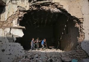 Mosul, Iraq Boys walk inside a destroyed mosque