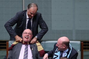 State of Origin rivalries bubble to the surface as John Alexander and Trent Zimmerman, both from New South Wales seats, playfully try to strangle Warren Entsch with his Queensland scarf before question time