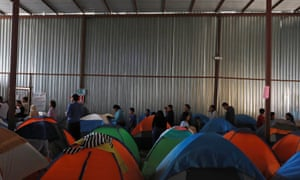Asylum seekers wait for food inside a shelter in Tijuana, Mexico on 6 April.