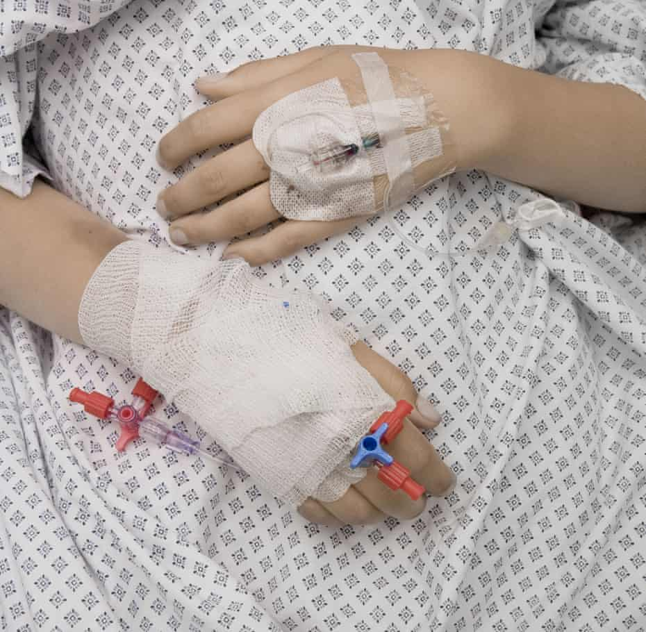 close up photograph of patient's hands in hospital bed