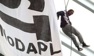 A protester hangs by a harness from the rafters during the second quarter of the game.