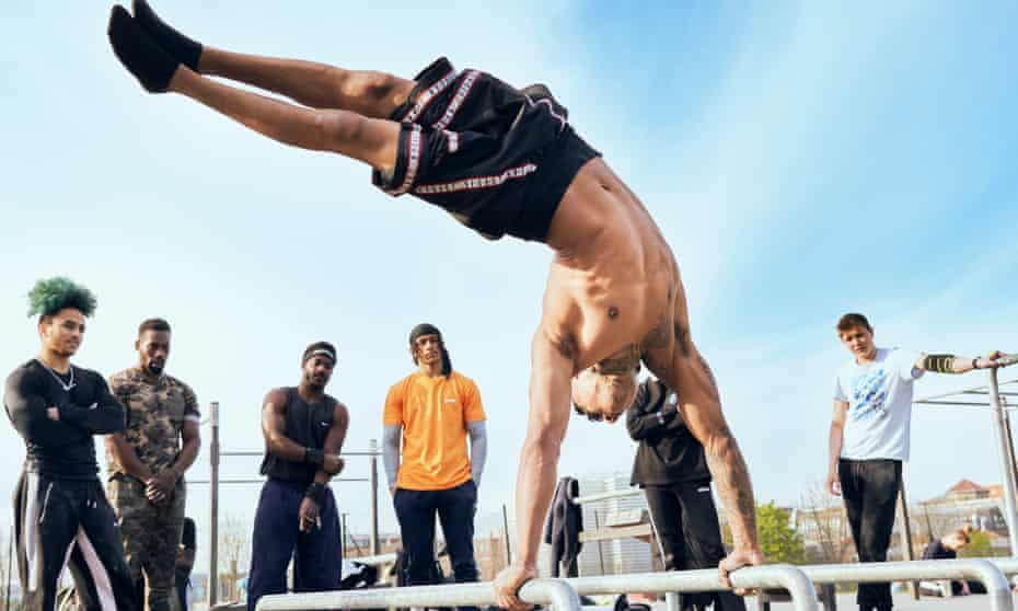 Chris Jay doing a handstand on bars in the outdoor gym with a small crowd watching
