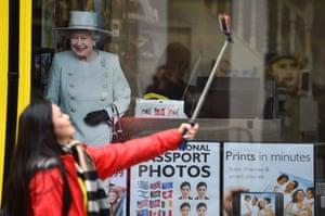 A woman takes a selfie beside an image of Britain's Queen Elizabeth II in a shop window near Windsor