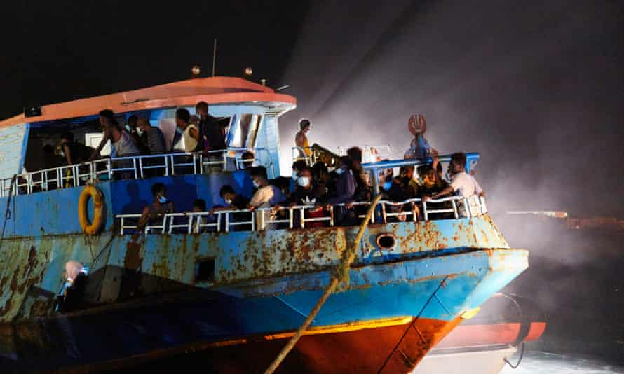 A fishing ship escorted by the Italian coastguard brings migrants to Lampedusa, Italy.