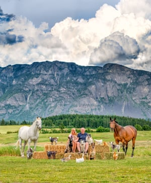 Mountains are in the background of this family and animals picture