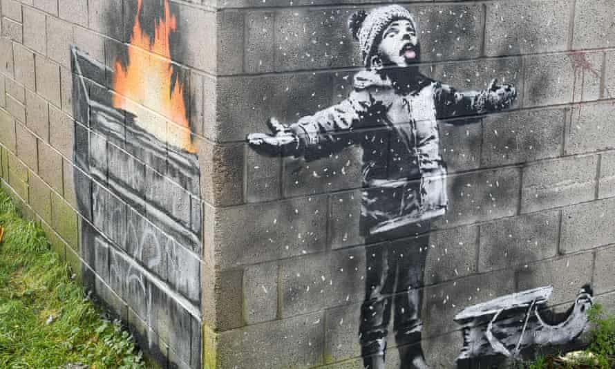 Banksy mural of child with arms and tongue out catching snow, with painting around the corner showing snow is actually ash from furnace