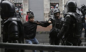 A demonstrator is detained by the police in Quito.