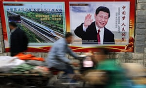 A man rides a tricycle past a poster featuring Chinese president Xi Jinping.