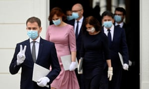 Igor Matovič, wearing a protective face mask, flashes a V-sign as he walks to pose for a group photo with newly appointed members of the Slovak government in Bratislava.