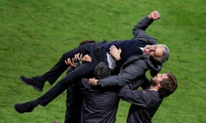 Manchester United manager Jose Mourinho is thrown in the air by his coaching staff.