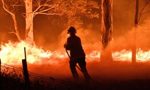A firefighter hosing down trees and flying embers in an effort to protect nearby houses from bushfires near the town of Nowra in the Australian state of New South Wales on 31 December