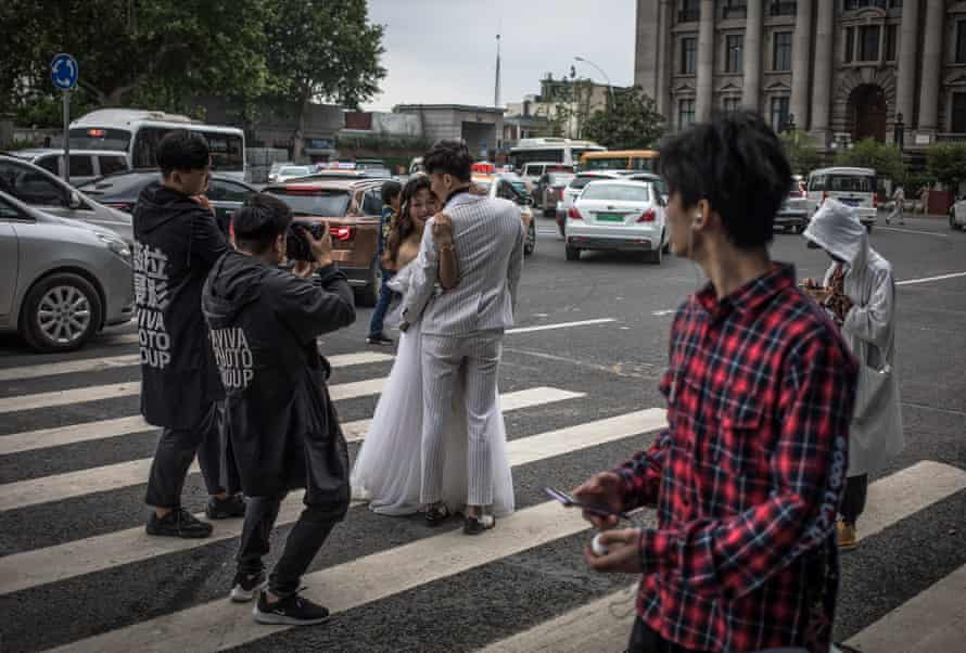 People pass by a couple posing for a photographer taking pre-wedding pictures on a road in Wuhan, China, 29 April
